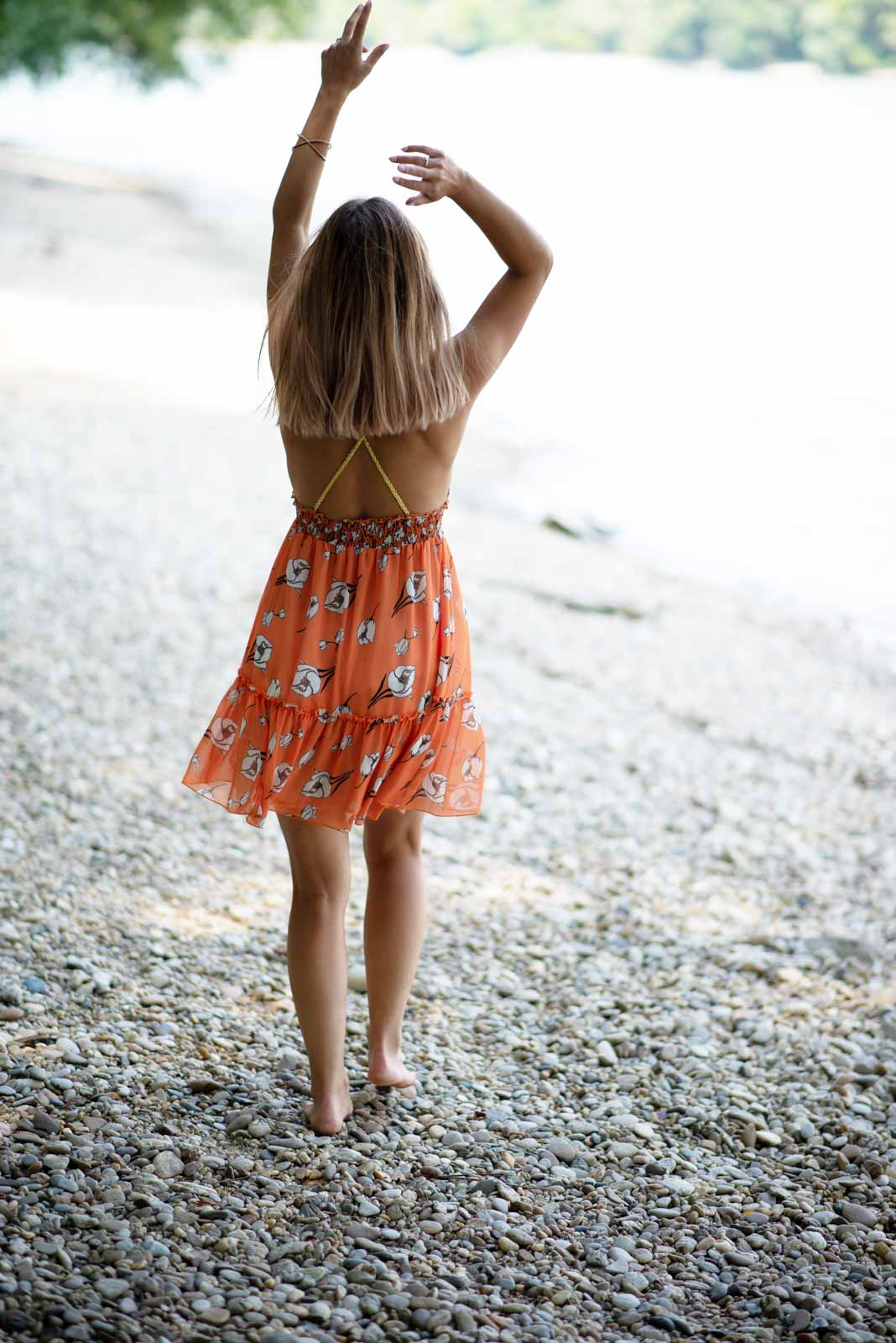 blonde girl on beach wearing orange dress