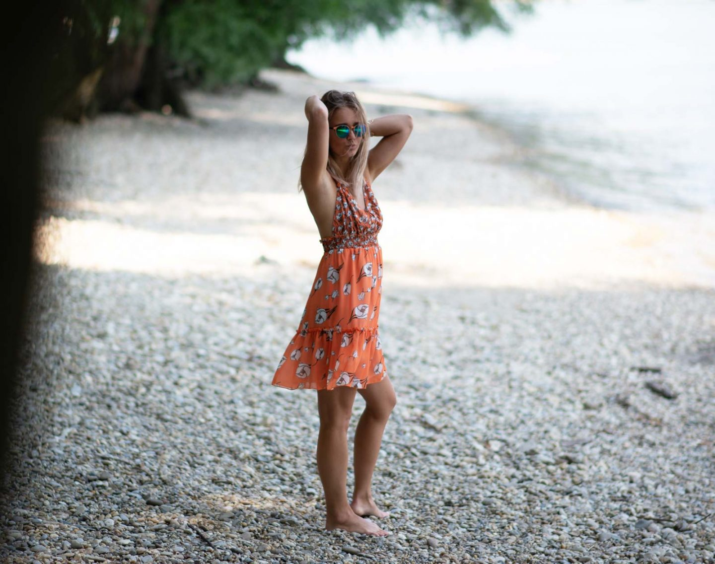 blonde girl standing on beach wearing mirror sunnies and orange dress