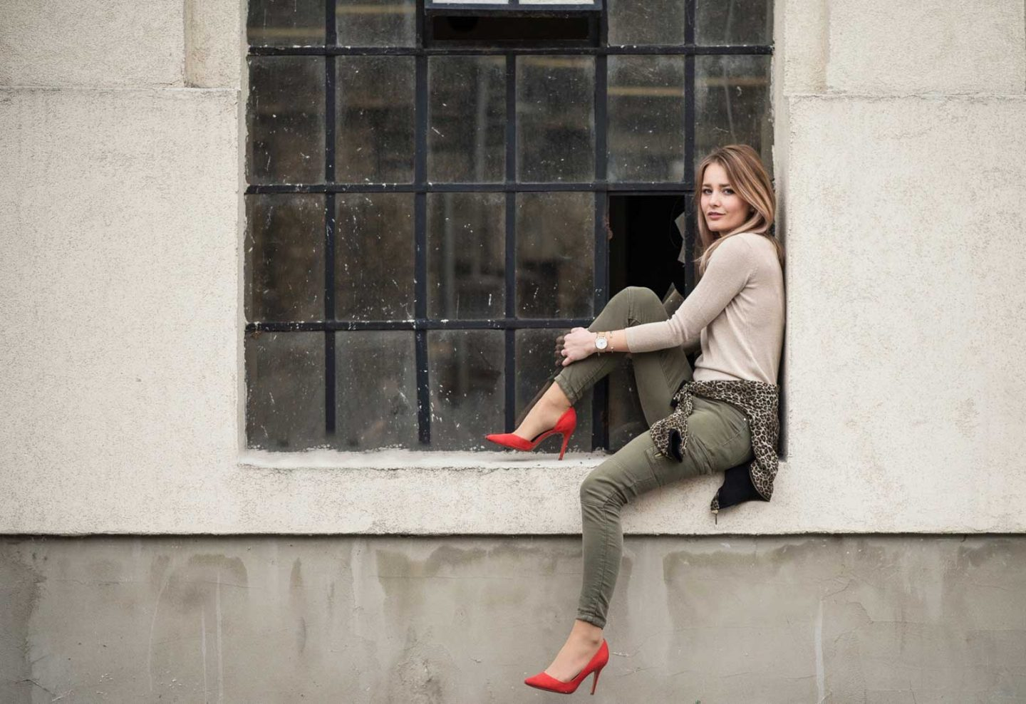 blonde girl wearing red heels sitting in industrial damaged window