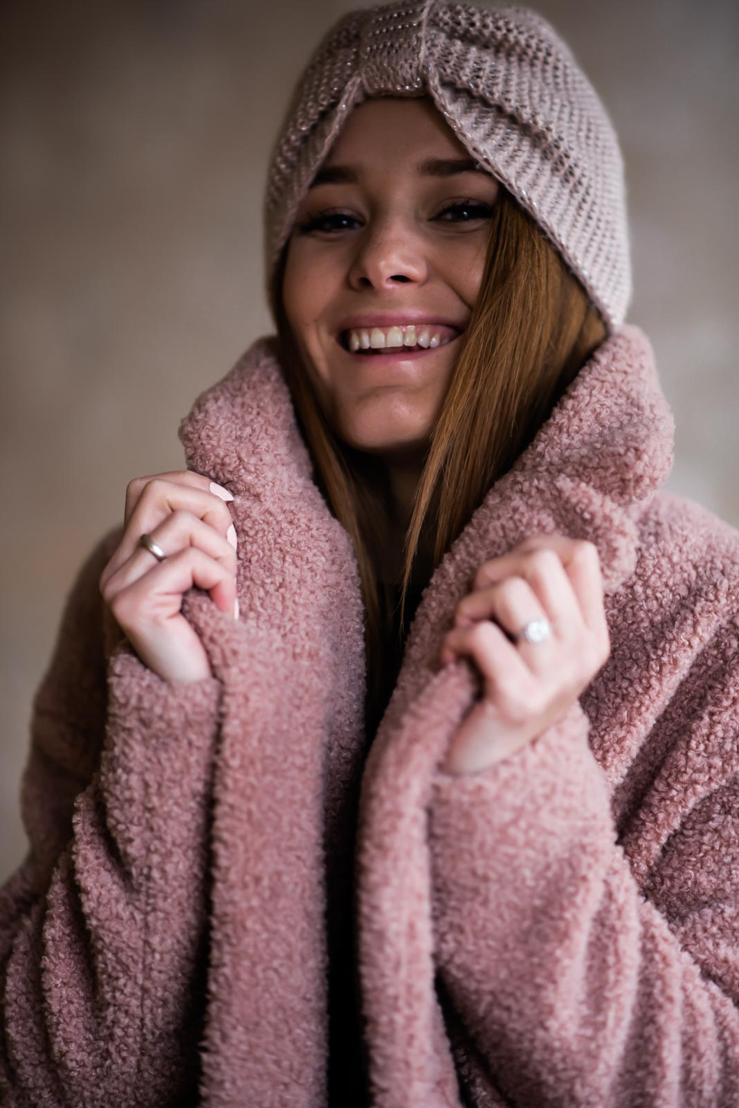smiling fashion blogger wearing pink turban and touching teddy coat