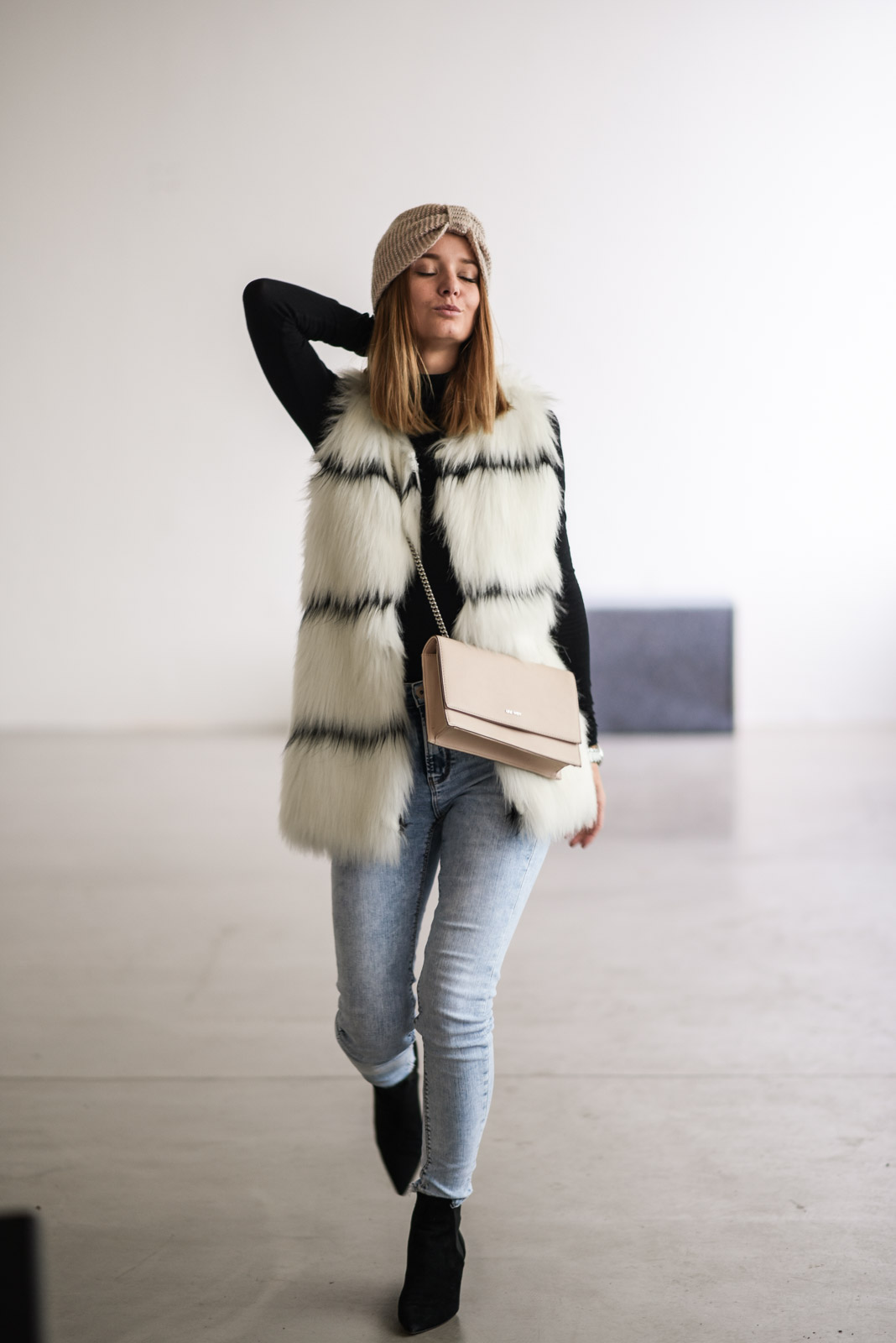 happy girl wearing fur vest walking and singing