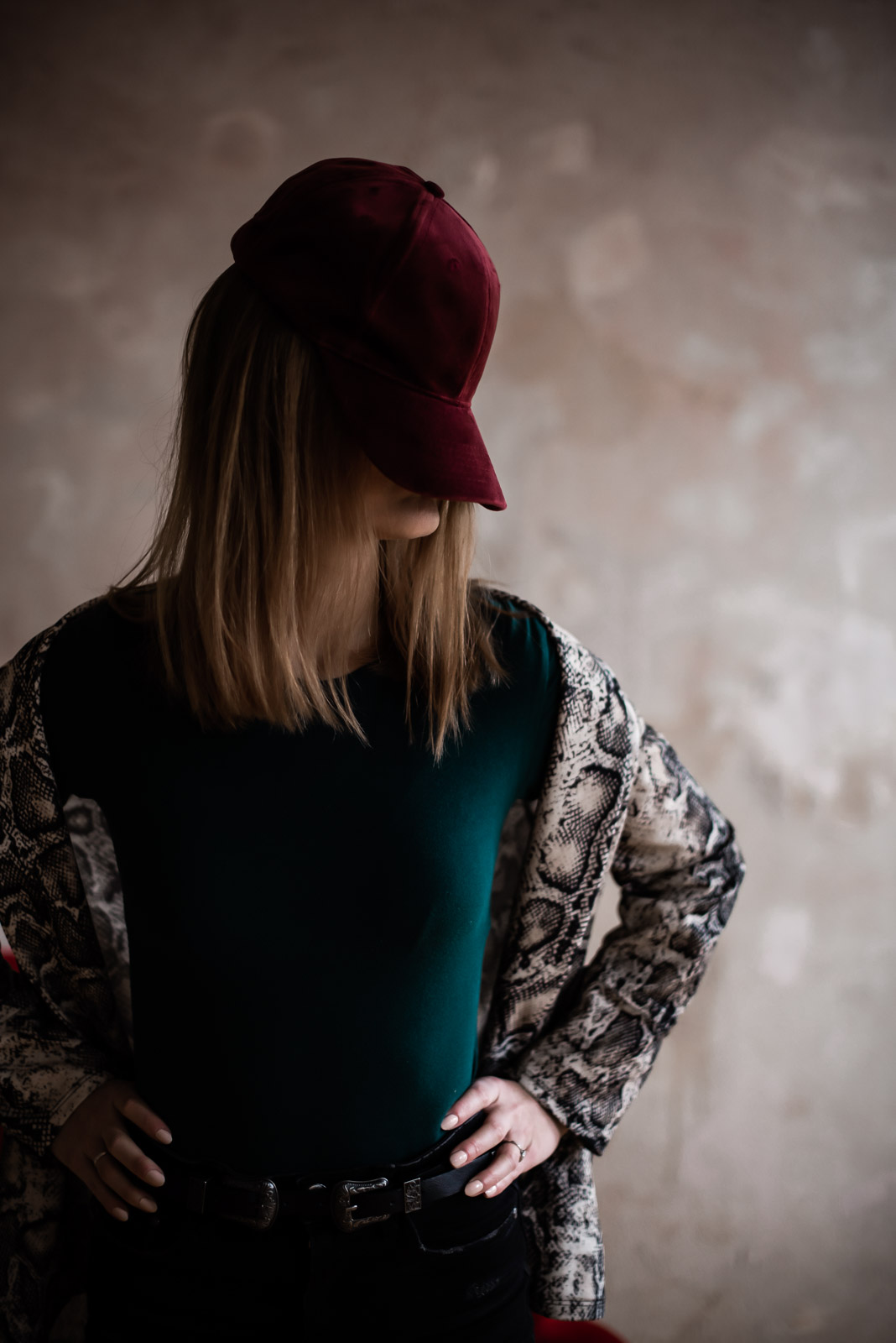 girl in snake print blazer and emerald top covering her face with baseball cap