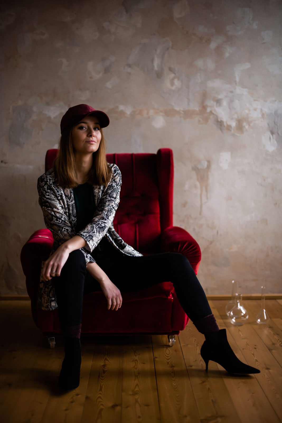 fashion blogger wearing snake print blazer sitting at red armchair
