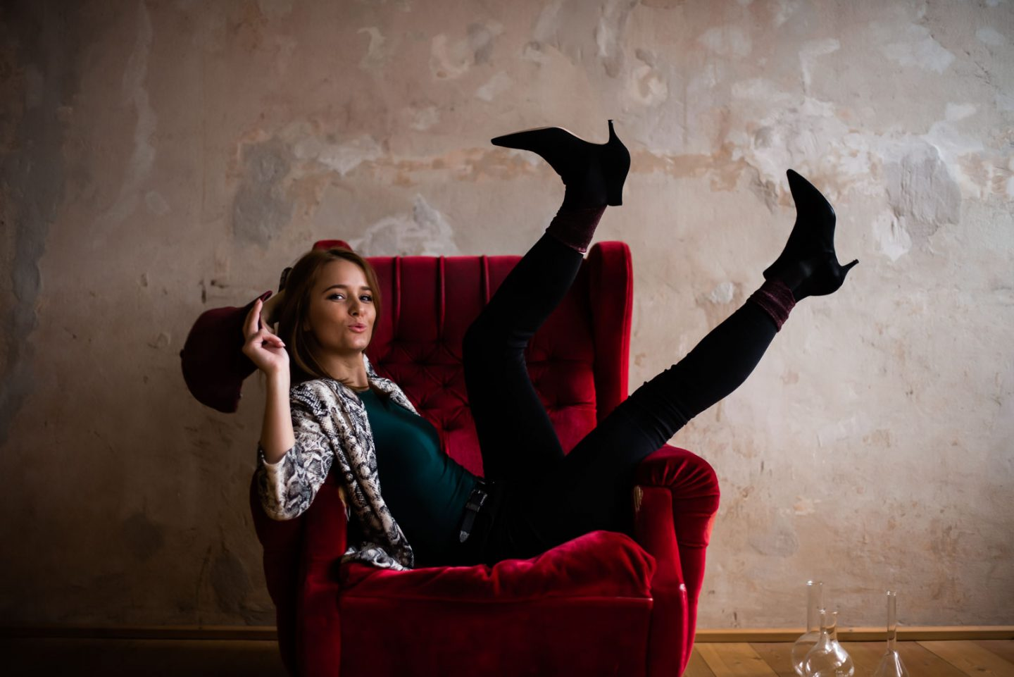 funny smiling women sitting on armchair with legs in the air